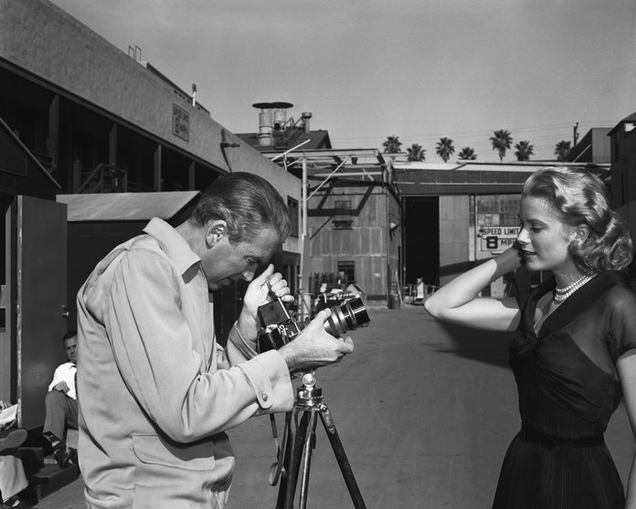 Jimmy Stewart pretends to photograph Kelly for Paramount publicity